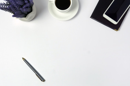 Minimalist concept - Top view of office desk with flower, pen, coffee smart phone and notepad on white background.