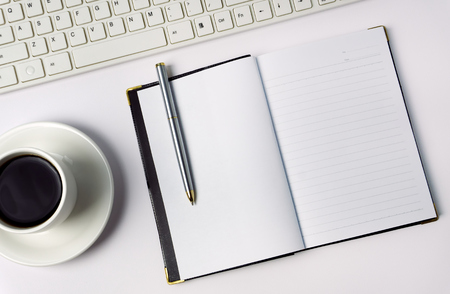 Minimalist concept - Top view of office desk with pen, coffee, computer keyboard and notepad on white background.