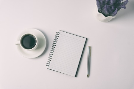 Minimalist concept - Top view of office desk with pen purse, flower and cup of coffee retro style.