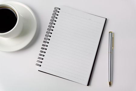 Minimalist concept - Top view of office desk wit cup of coffee, open notepad and pen on white background