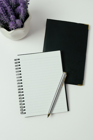 Minimalist concept - Top view of office desk with open notepad, pen and flower, retro style.