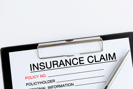 Photo pour Insurance Claim Form on attached on Clip board and pen on white background - image libre de droit