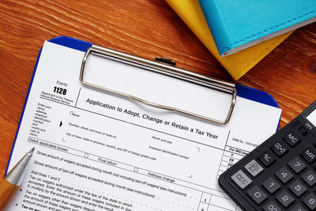 Photo pour Form 1128 Application to Adopt, Change or Retain a Tax Year sign on the piece of paper. - image libre de droit