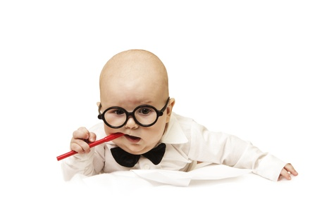 The thoughtful small baby gnaws pen