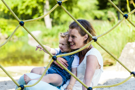 Mutter und Kleinkind zusammen auf dem Spielplatz draussen.