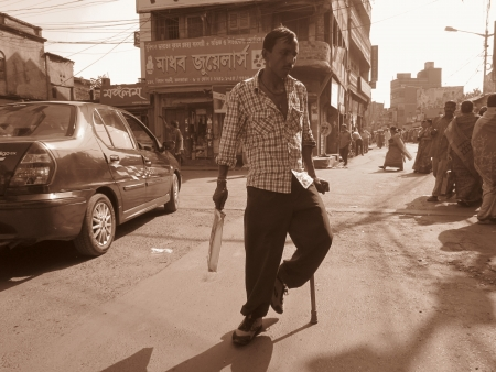 PHYSICALLY CHALLENGED CROSSING ROAD.SHOT AT CALCUTTA, INDIA: AFTERNOON HOURS ON NOVEMBER 14,2012.