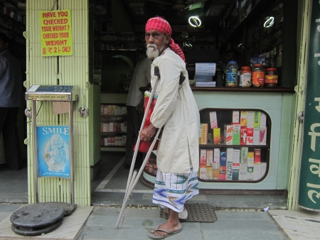 PHYSICALLY CHALLENGED MAN BEGGING IN A SHOP.SHOT AT CALCUTTA INDIA: MORNING HOURS ON NOVEMBER 12,2012.