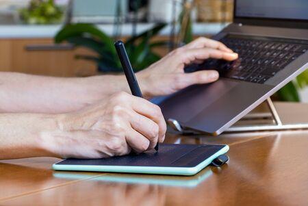 Foto de Female designer hands using a drawing graphics tablet and a laptop while working at home. - Imagen libre de derechos