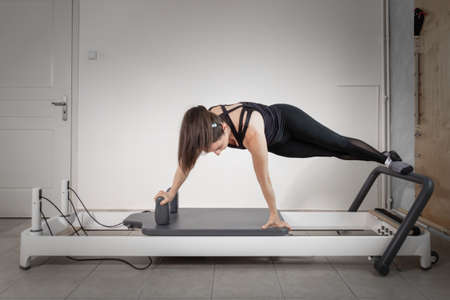 Photo for A woman doing pilates exercises with a reformer bed at her private gym. - Royalty Free Image