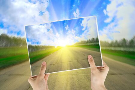 Hand holding photo of road background with sunrise