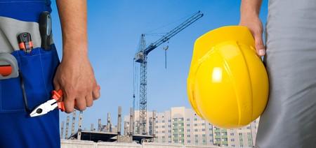 Photo pour Closeup of workers with instruments on building background - image libre de droit