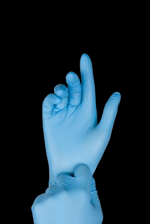 Blue gloves on a hand on a black background