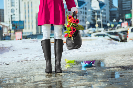 Woman wearing rain boots stay into a puddle