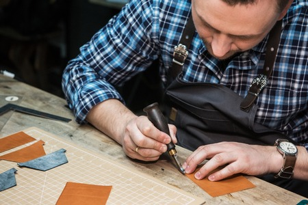 Man working with leather textile at a workshop. Concept of handmade craft production of leather goods.