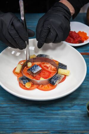 Photo pour Process of cooking escabeche fish dish with caviar: mackerel in marinade with vegetable, on a plate on the wooden blue background. - image libre de droit