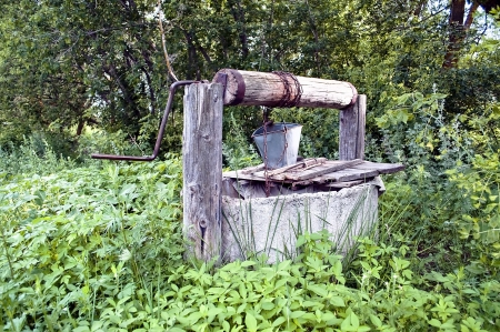 Old countryside water well with a bucket