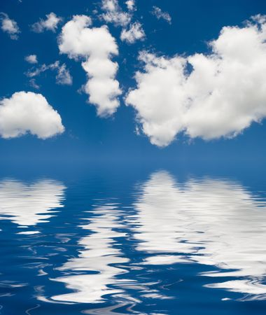 blue sky covered by clouds reflected in water