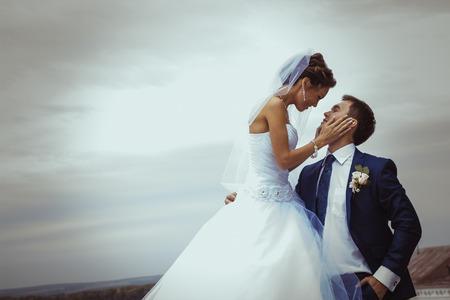 Foto de Young wedding couple kissing  Bright white colors  - Imagen libre de derechos
