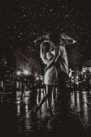 Photo pour happy couple kissing under  the rain - image libre de droit