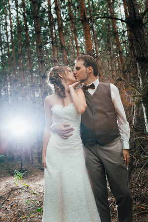 dramatic picture bride and groom on the background of leaves and forest backlight.の写真素材