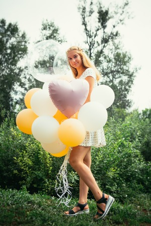 young girl with balloons on nature background.