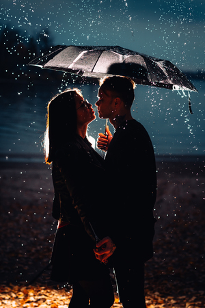 Photo pour young man and woman under an umbrella and rain. - image libre de droit