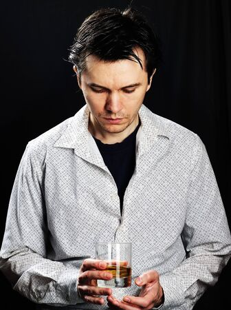 Man wearing the white shirt with glass of whiskey in the hand. Black background.