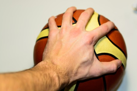 Male hand holding a basketball
