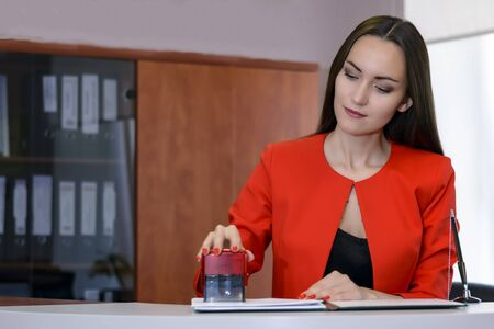 A female Boss in a bright red business suit puts a seal to the contract at the reception office