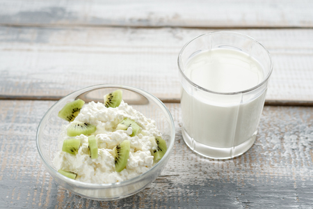 Frontally on a grey wooden background cottage cheese in a bowl with kiwi fruit, soft counter light, healthy food concept.