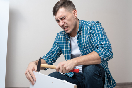 Photo for man in casual clothes hit his thumb with a hammer when assembling furniture, difficulty, emotion of pain. - Royalty Free Image