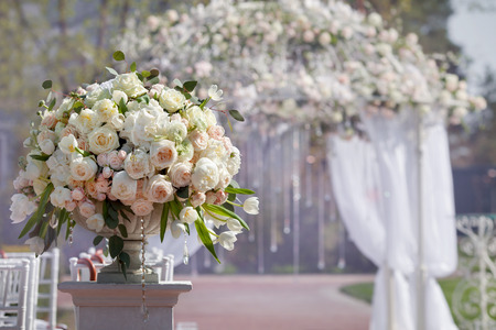 Photo pour Beautiful bouquet of roses in a vase on a background of a wedding arch. Beautiful set up for the wedding ceremony. - image libre de droit