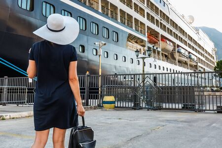 Photo pour Happy lady in white hat and blue dress going on the cruise at Kotor, Montenegro. Rear view. Bay of Kotor bay is one of the most beautiful places on Adriatic Sea. - image libre de droit