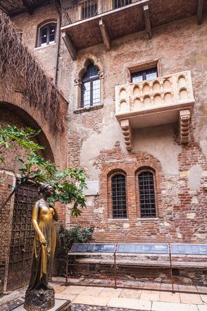 Photo pour Patio and balcony of Romeo and Juliet house at golden sunset, Verona, Italy. Bronze statues of Juliet. - image libre de droit