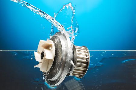 Auto parts, engine cooling pump in water splash on blue gradient background