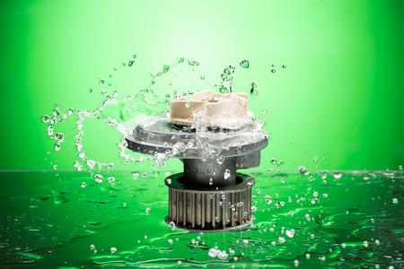 Auto parts, engine cooling pump in water splash on green gradient background