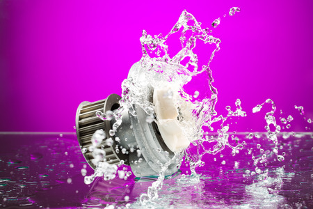 Auto parts, engine cooling pump in spurts of water on purple gradient background