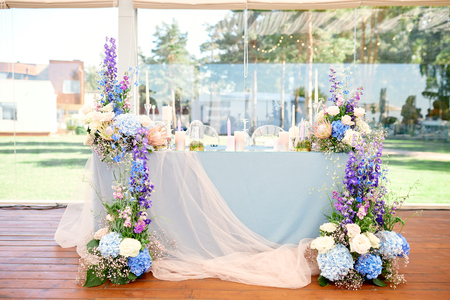 Photo pour wedding table for newlyweds, very beautifully decorated with flowers and candles and a tablecloth - image libre de droit