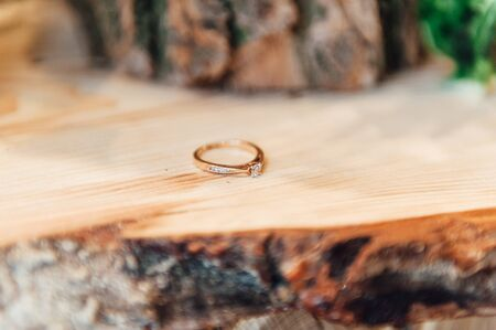 Wedding rings on the wooden frame with bokeh background