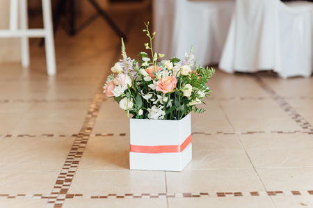 Beautiful bouquet of bright flowers in basket for wedding ceremony