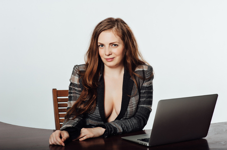 Sexy business woman in a jacket with a big neckline and chest sits on a chair and works with a laptop