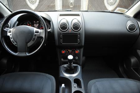 Foto de Modern luxury prestige car interior, dashboard, steering wheel. Black perforated leather interior. plastic panels. Isolated windows - Imagen libre de derechos