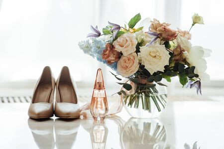Photo pour wedding set of the bride. Beige shoes, perfume and a beautiful bouquet are on the marble floor - image libre de droit