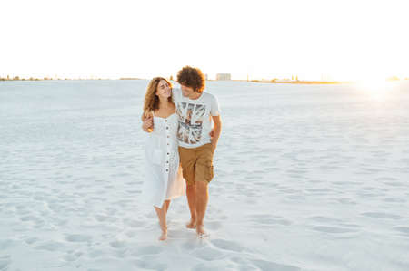 Photo for Vacation couple walking on beach together in love holding around each other. - Royalty Free Image