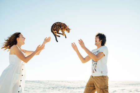 Photo pour Cheerful young couple having fun on the beach with their bengal cat - image libre de droit