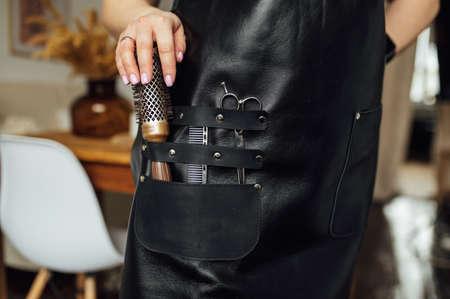 Foto für Person in black apron with professional hairdresser set on dark background, closeup - Lizenzfreies Bild