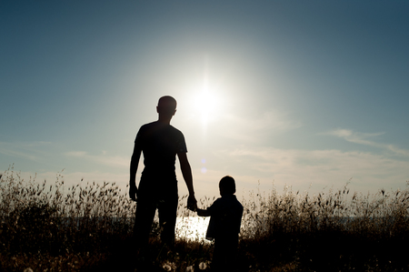 Silhouette of father and small son against the background of sea sunset