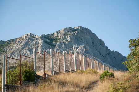 high fence for illegal immigrants barbed wire at state border in rocky mountains in sunny day