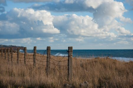 empty place near sea coast with barbed wire fence on border with blue sky and clouds on overcast sunset