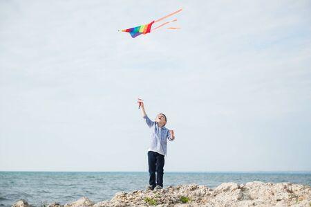 Foto de active happy little boy holding flying colorful kite flying in air standing on rock sea shore on summer sunny day - Imagen libre de derechos